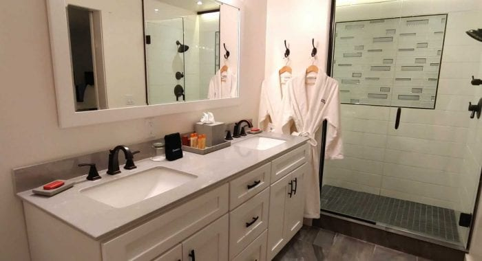 Suite Getaway Bathroom vanity with shower and robes